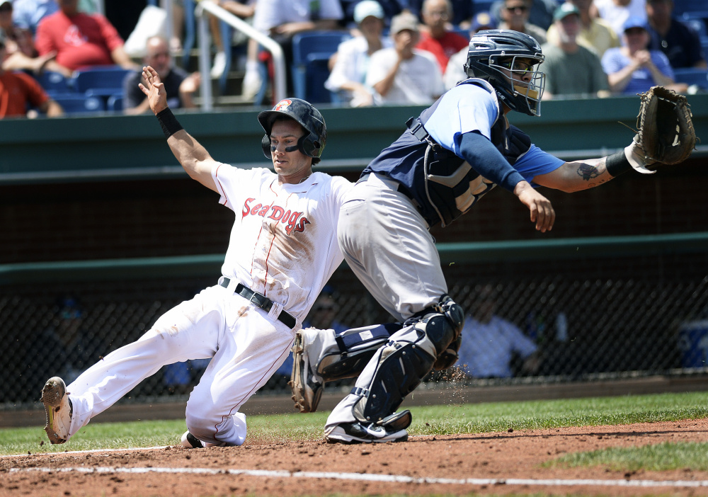 Portland's Ryan Court slides safely into home plate as Trenton catcher Sebastian Valle waits for the throw Wednesday at Hadlock Field. Trenton went on to a 10-6 win.
