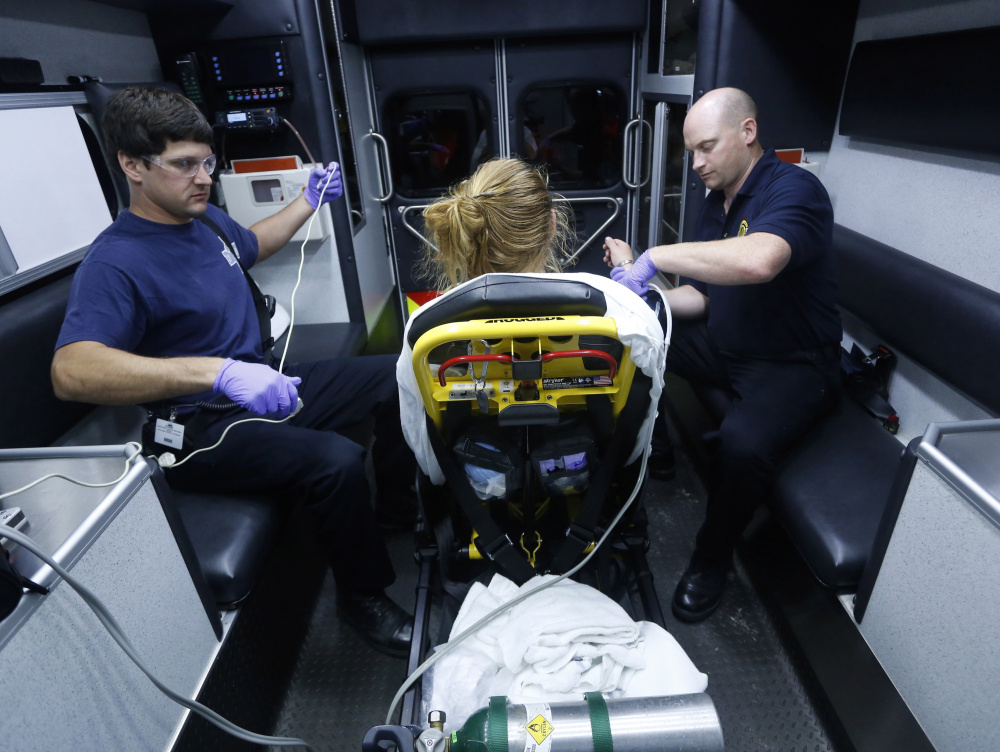 Portland paramedics Steven Bishop, left, and Nathaniel Sparling monitor a woman whom they revived Aug. 12, 2015, after she was found unconscious from a heroin overdose. Maine is the only New England state that doesn't offer some sort of immunity from prosecution for people who seek medical assistance for someone experiencing an overdose.