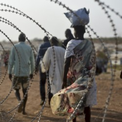 People walk next to a razor wire fence at the United Nations base in the Juba, South Sudan, last January. Ethnic Nuer women and girls were reportedly raped near here last week.