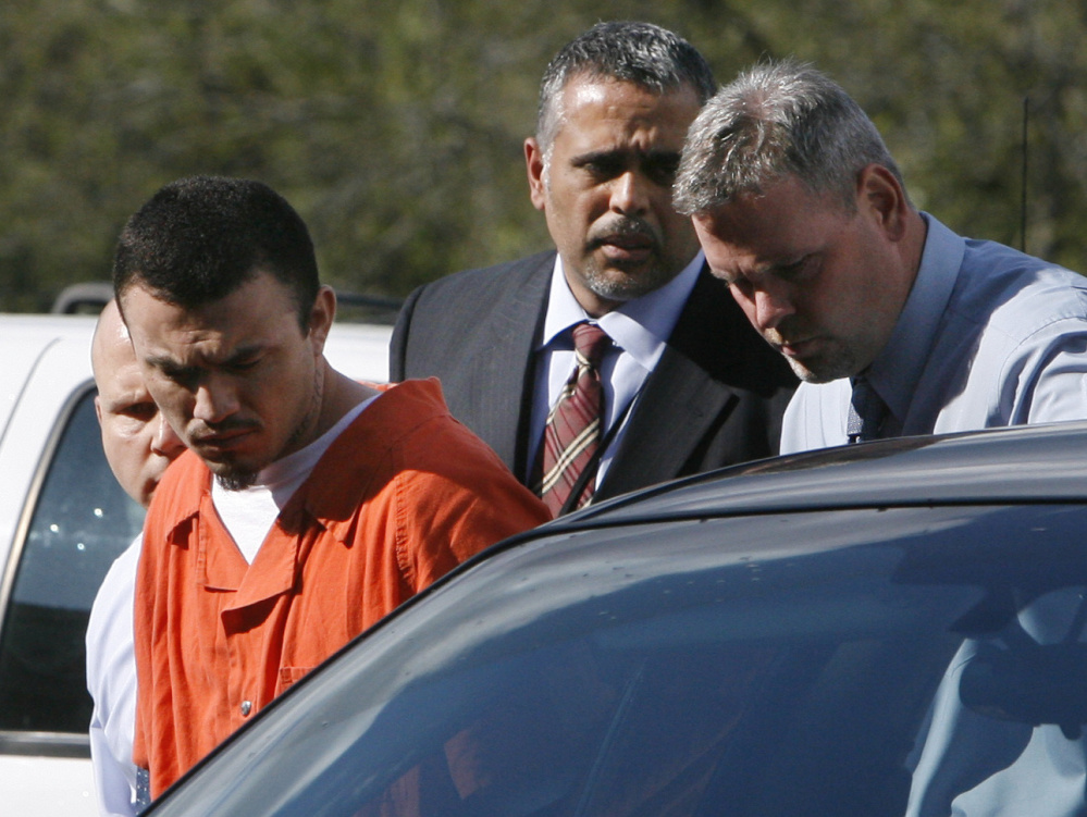 Ingmar Guandique, 27, left, who was accused of killing Chandra Levy, is escorted into the Violent Crimes Unit by detectives Emilio Martinez, and Todd Williams, right, in Washington, on Wednesday, April 22, 2009. At far left is detective Anthony Brigidini.