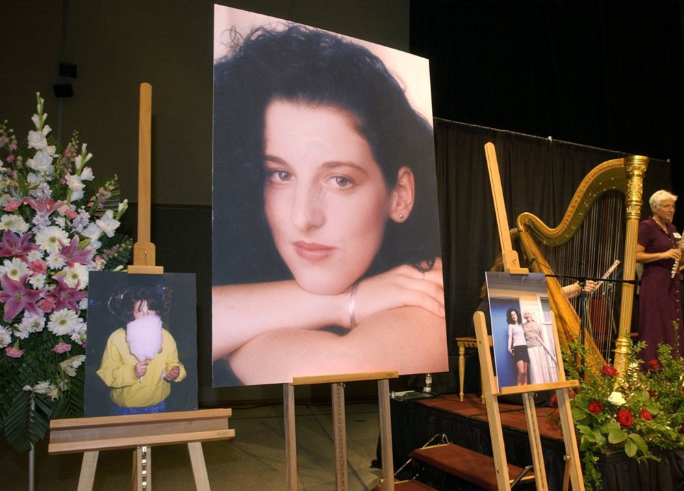 FILE - In this May 28, 2002 pool-file photo taken at the Modesto Centre Plaza in Modesto, Calif., photos of Chandra Levy are on display as musicians, right, stand by at the memorial service for Levy. Prosecutors say they will not retry a man convicted of killing Washington intern Chandra Levy. The U.S. Attorney's office said in a statement Thursday, July 28, 2016, that the office has moved to dismiss the case charging Ingmar Guandique with Levy's 2001 murder. According to the statement, prosecutors concluded they could not convict Guandique