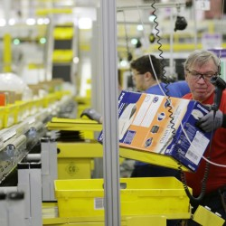 Workers process outgoing orders at Amazon.com's fulfillment center in DuPont, Wash. The company has announced plans for 17 new distribution centers in the U.S. alone since March, and has 123 centers worldwide.