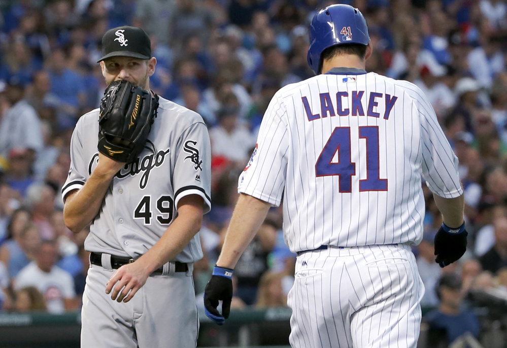 Pitcher Chris Sale, left, of the White Sox and pitcher John Lackey of the Cubs pass each other after Sale fielded a ground ball by Lackey and threw him out first to end the second inning. The Cubs won, 3-1, at Wrigley Field.