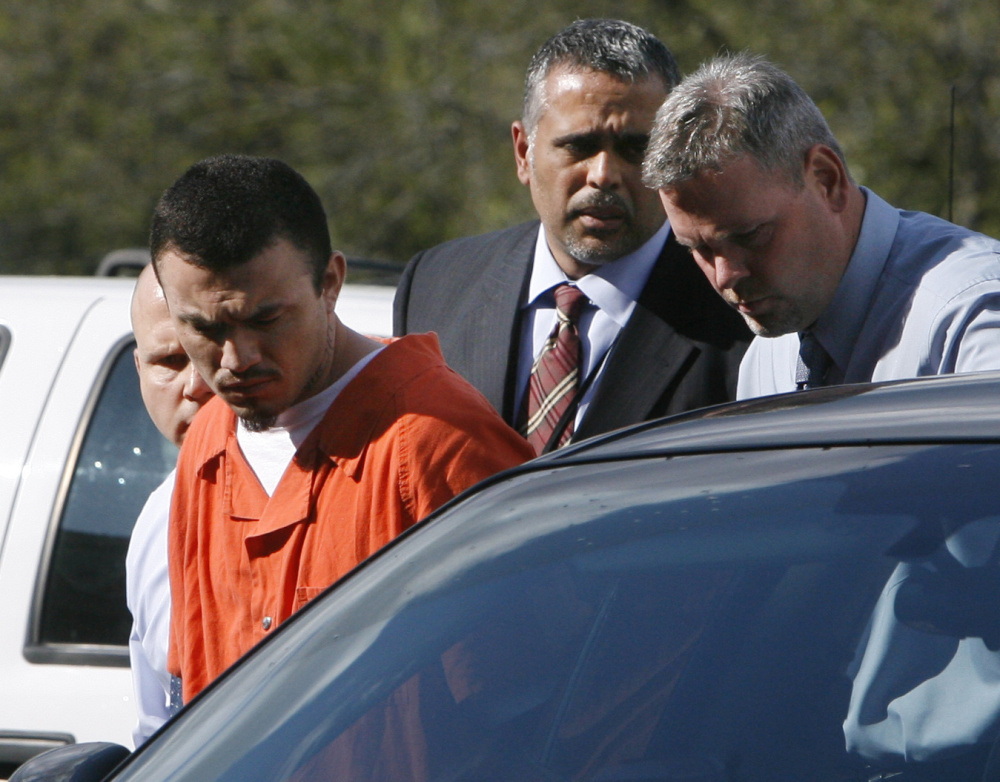 Ingmar Guandique is escorted detectives in 2009. He was convicted of Levy's murder in 2010. On Thursday, all charges against him were dropped. Associated Press/Jacquelyn Martin