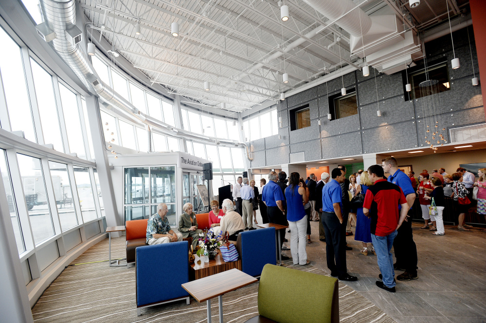 People mingle as Northeast Air unveils its new facility Friday. The company, which has been operating out of the Portland jetport's original 1950s-era passenger terminal, says its new terminal will boost economic development by making a good first impression as the wealthy arrive on private jets.