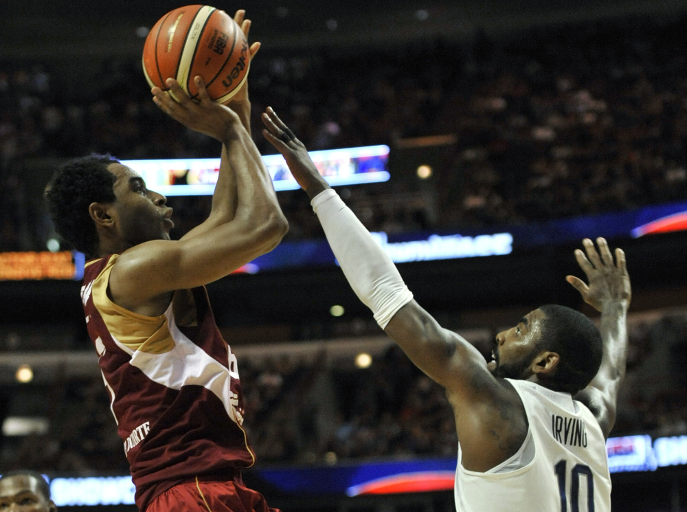 John Cox of Venezuela lofts a shot over Kyrie Irving of the United States during the first half of the U.S.' 80-45 victory Friday night in a men's basketball tuneup in Chicago before the Olympics.