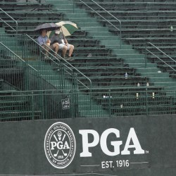 Two fans sit only in the grandstand on the 18th green during a weather delay in the third round of the PGA Championship at Baltusrol Golf Club in Springfield, N.J. on Saturday.