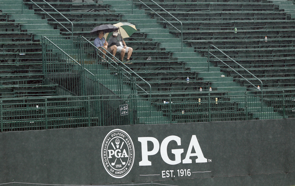 Two fans sit in the grandstand on the 18th green during a weather delay in the third round of the PGA Championship at Baltusrol Golf Club in Springfield, N.J. on Saturday.