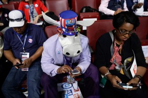 Rodney McFarland Sr. wears a donkey hat as he check his phone before the start of the second day session of the Democratic National Convention in Philadelphia on Tuesday.
