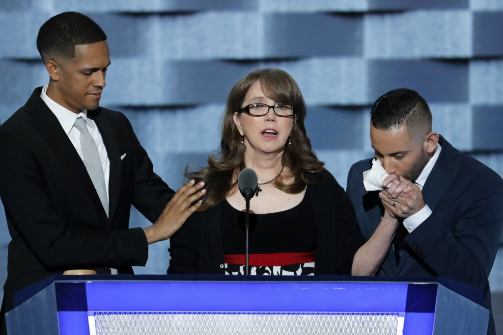 """Christine Leinonen, the mother of Christopher """"Drew"""" Leinonen, who was killed in the nightclub attack in Orlando, is joined on stage by Brandon Wolf and Jose Arraigada, survivors of the attack, as she speaks during the third day of the Democratic National Convention in Philadelphia , Wednesday, July 27, 2016."""