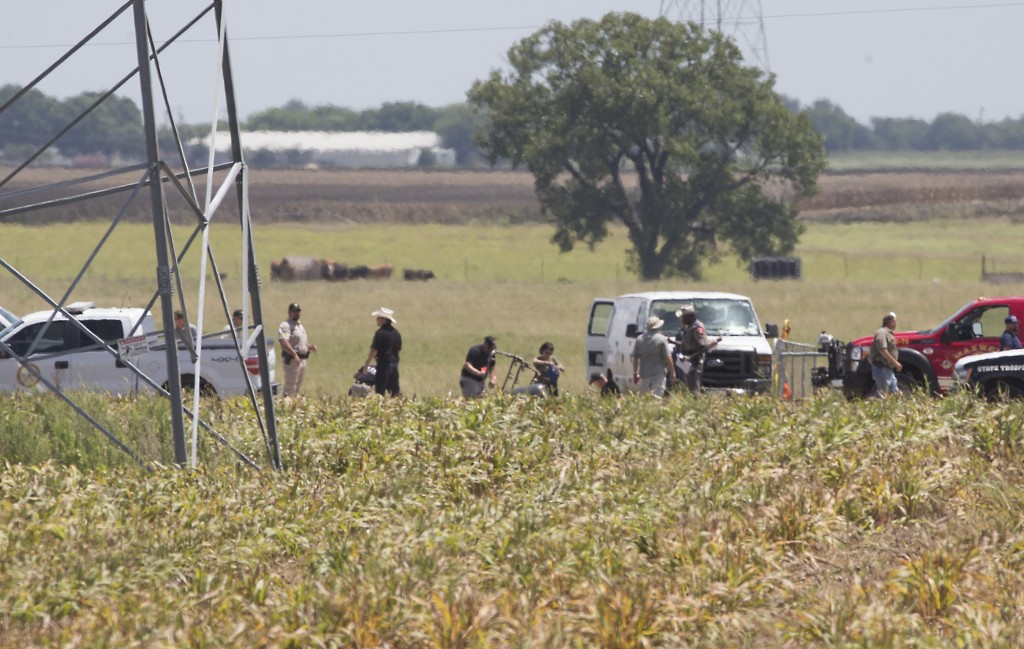 The partial frame of a hot air balloon is visible at the scene in a field near Lockhart, Texas, where a hot air balloon carrying at least 16 people collided with power lines Saturday, causing what authorities described as a
