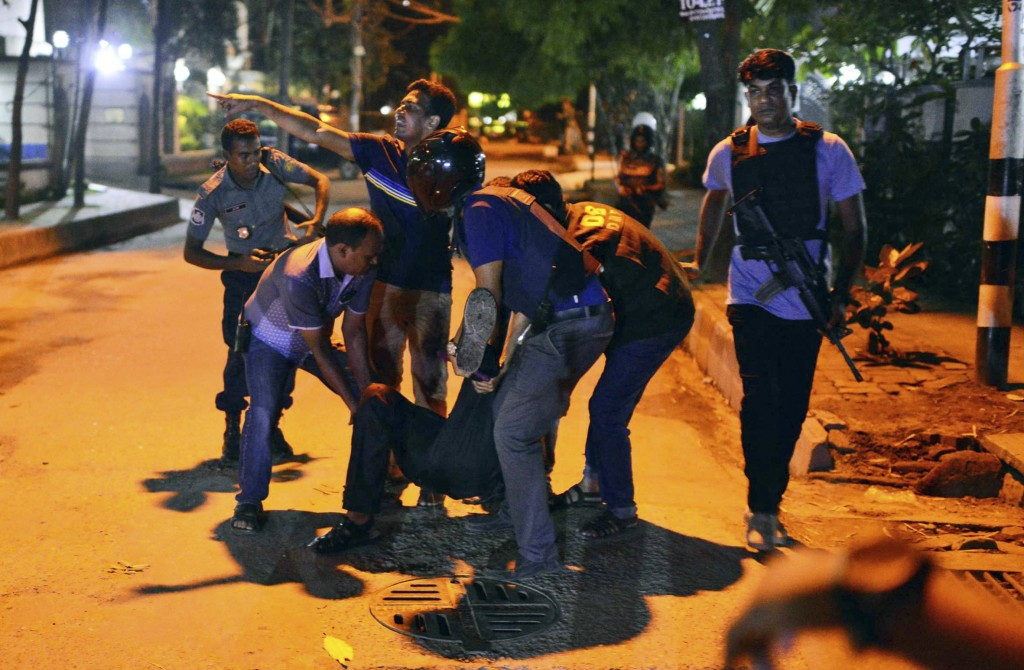 People help an injured person after gunmen attacked a restaurant in the Bangladeshi capital of Dhaka. The militants took hostages and exchanged gunfire with security forces before commandos ended the siege early Saturday. Associated Press photo