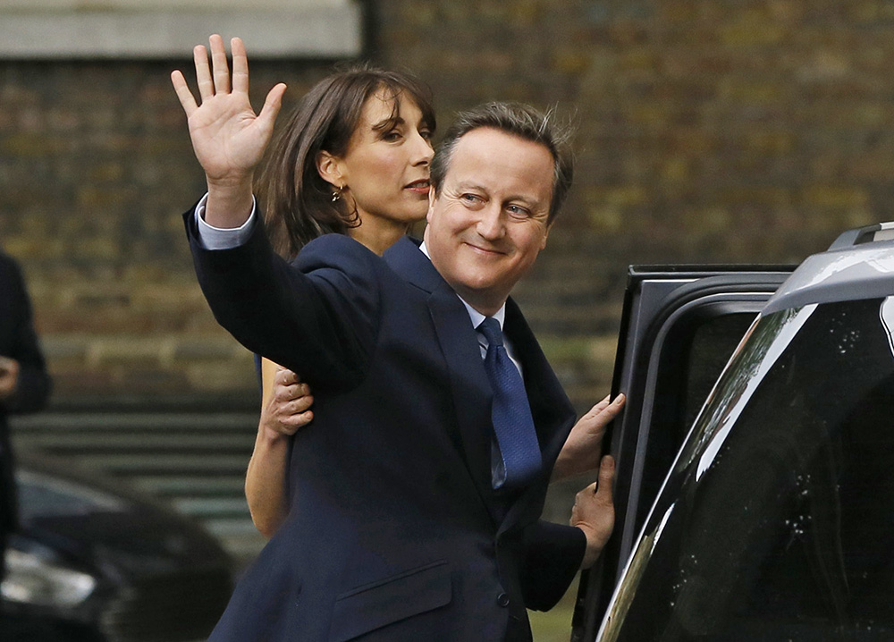 David Cameron, with his wife Samantha, waves to the media as leaves 10 Downing Street in London for the last time, Wednesday. Associated Press