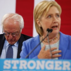 Sen. Bernie Sanders, I-Vt. listens as Democratic presidential candidate Hillary Clinton speaks during a rally in Portsmouth, N.H., Tuesday, at which Sanders endorsed Clinton for president.