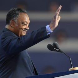 The Rev. Jesse Jackson waves from the podium during the third day of the Democratic National Convention in Philadelphia on Wednesday. He said Hillary Clinton can be trusted to fight for issues such as a fair Supreme Court, gun control and progressive policies.