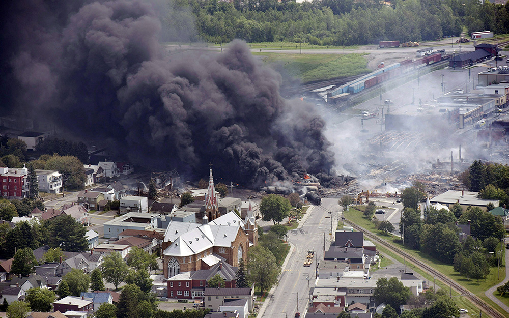 Smoke rises from oil tanker cars after they derailed in downtown Lac Megantic, Quebec, in 2013. The derailment killed 47 people and burned 30 buildings in the town's center. Paul Chiasson/The Canadian Press via AP