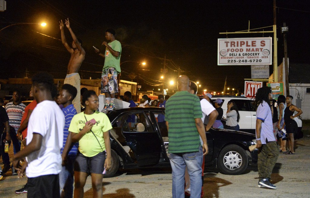 Protesters gather near the Triple S Food Mart after Alton Sterling was shot and killed by Baton Rouge police in early Tuesday morning. Officers went to the store after an anonymous caller indicated a man selling music CDs and wearing a red shirt threatened him with a gun, said Cpl. L'Jean McKneely.  Hilary Scheinuk/The Advocate via AP