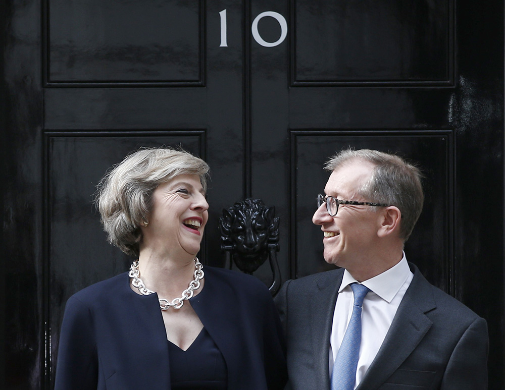 """Theresa May and husband Philip pose for the media outside number 10 Downing St., in central London, Wednesday. May was expected to begin appointing new Cabinet ministers as early as Wednesday evening — including a """"Brexit"""" minister to oversee talks on a British EU exit from the 28-nation EU."""