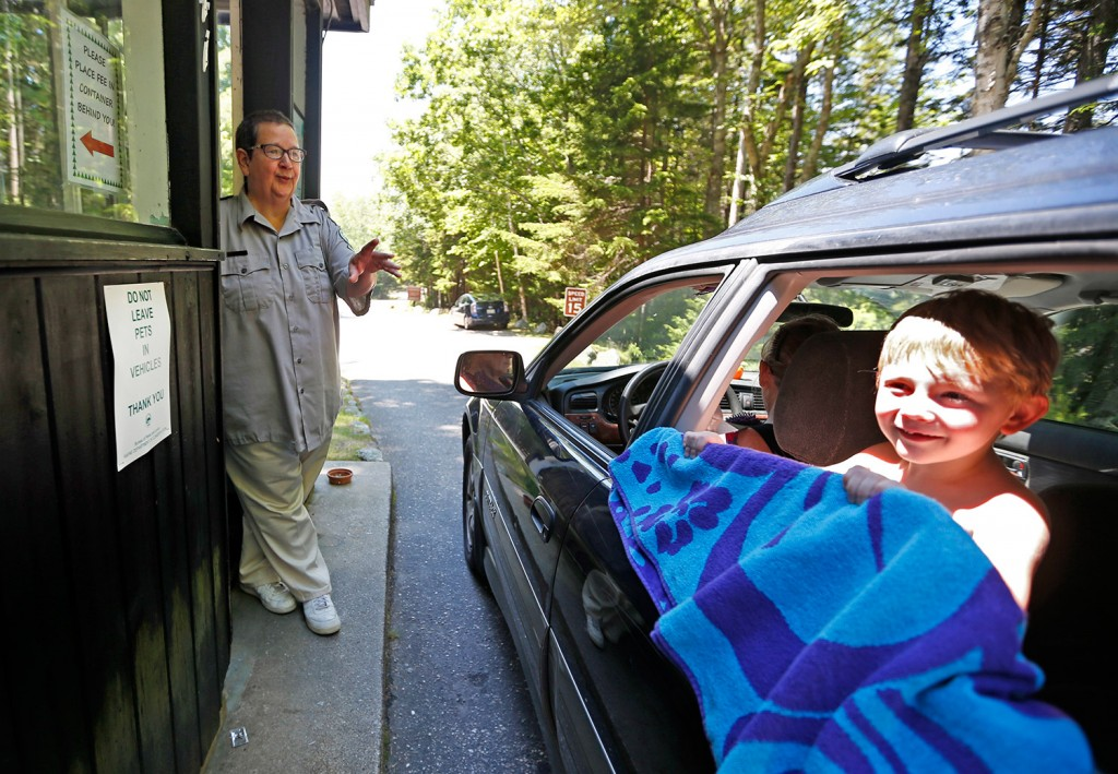 Sarah Crosby speaks to a visitor heading to the beach at Reid State Park. She has worked the entryway to Maine's oldest state-owned beach for 44 years, and has no plans to stop. Associated Press/Robert F. Bukaty