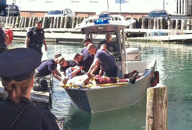 Emergency personnel with the Portland Fire Department attend to a man who fell into the water at Custom House Wharf Saturday morning. Photo by Peter McGuire/Staff Writer