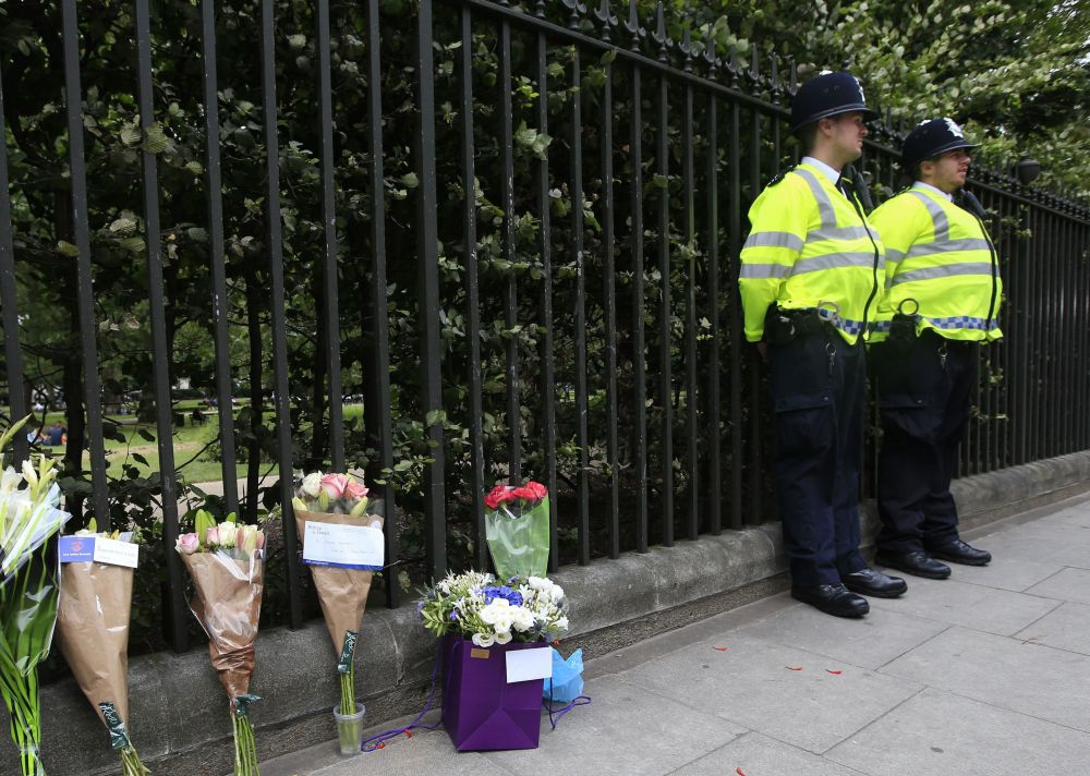 Floral tributes rest against railings Thursday near the scene of stabbings Wednesday night in Russell Square, London, that left a Florida woman dead and five others injured.