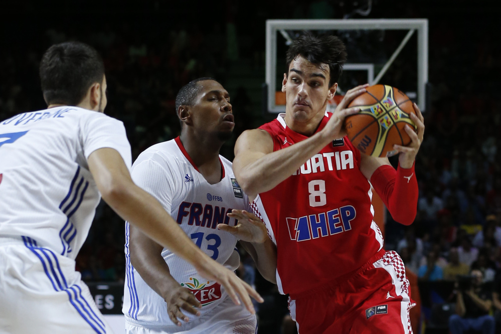 Croatia's Dario Saric, right, drives the ball against France's Boris Diaw, center, and Joffrey Lauvergne during a game in 2014. Saric is one of the players worth watching during the Olympics.