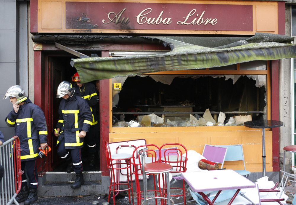 Firefighters walk out of a bar where a fire broke out in Rouen, France. A fire swept through a Friday night birthday party at the bar, killing at least 13 people and injuring six others.