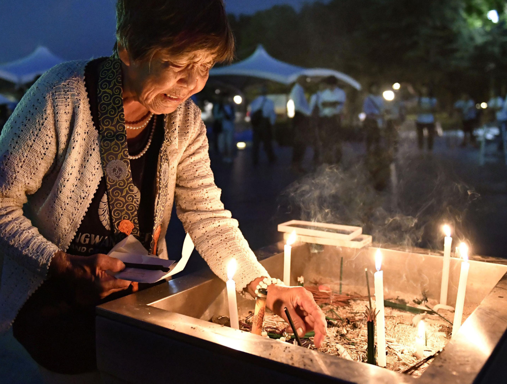 A woman lights a candle as she prays for the atomic bomb victims at the Hiroshima Peace Memorial Park.