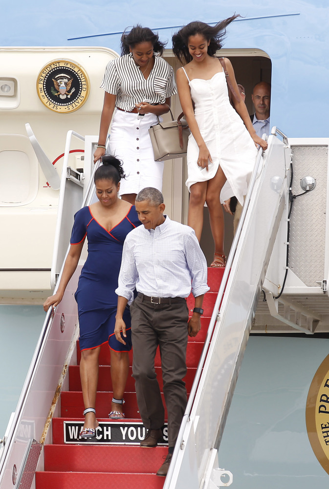 President Obama and first lady Michelle Obama exit Air Force One followed by daughters Sasha, left, and Malia, right, at the Cape Cod Coast Guard Station in Bourne, Mass., on Saturday en route to Martha's Vineyard. (AP Photo/Stew Milne)