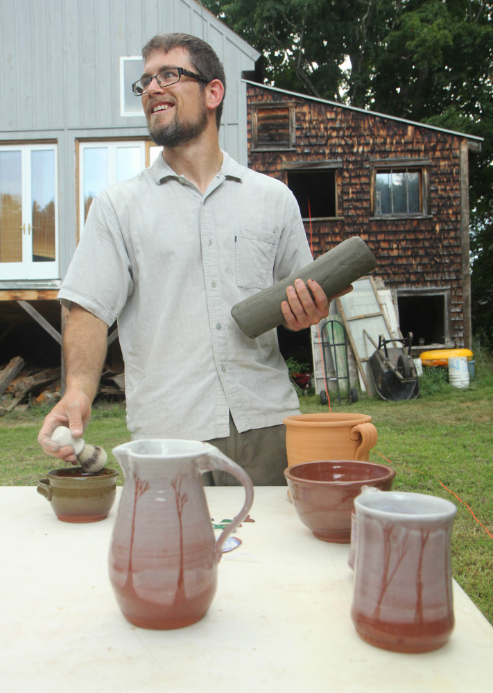 Jon Lamarche holds some processed pottery clay in front of some his works behind Wayne Village Pottery. The Saunders' family, which runs the pottery business, was hoping to dig up 40 tons of clay on Saturday and have enough to last five to 10 years until the next dig. Lamarche owns the nearby Old Firehouse Farm gift shop and cafe but helps out at Wayne Village Pottery in exchange for pottery clay.