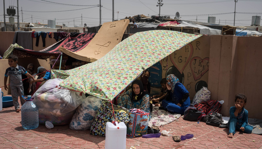 Iraqis rest under an improvised tent in a yard where they have been sleeping at the Dibaga camp for displaced civilians. As many as 3,000 people have arrived here in the last week.