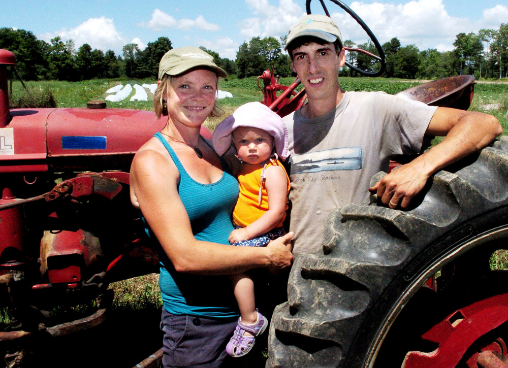 Johanna Burdet and Jarret Haiss, with 18-month-old Tiger, cultivate organic vegetables and make hay at Moodytown Gardens in Palmyra. David Leaming/Morning Sentinel