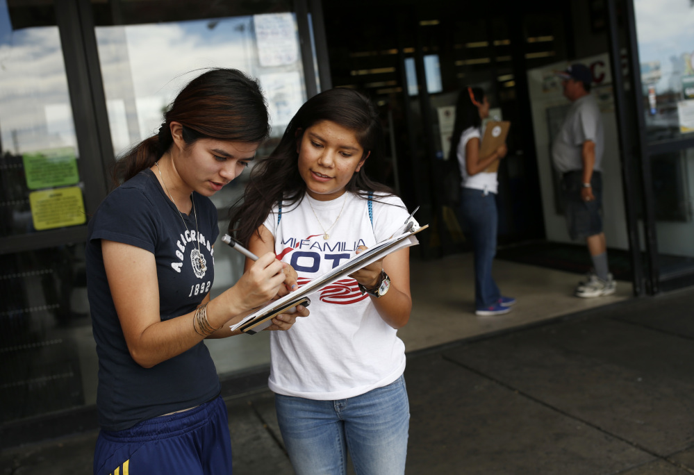 Fabiola Vejar, right, registers Stephanie Cardenas to vote in June in Las Vegas. Shielded from deportation under an Obama administration program that protects those brought to the country illegally as children, Vejar, 18, cannot vote. So she volunteers with Mi Familia Vota, encouraging others to be heard at the ballot box.