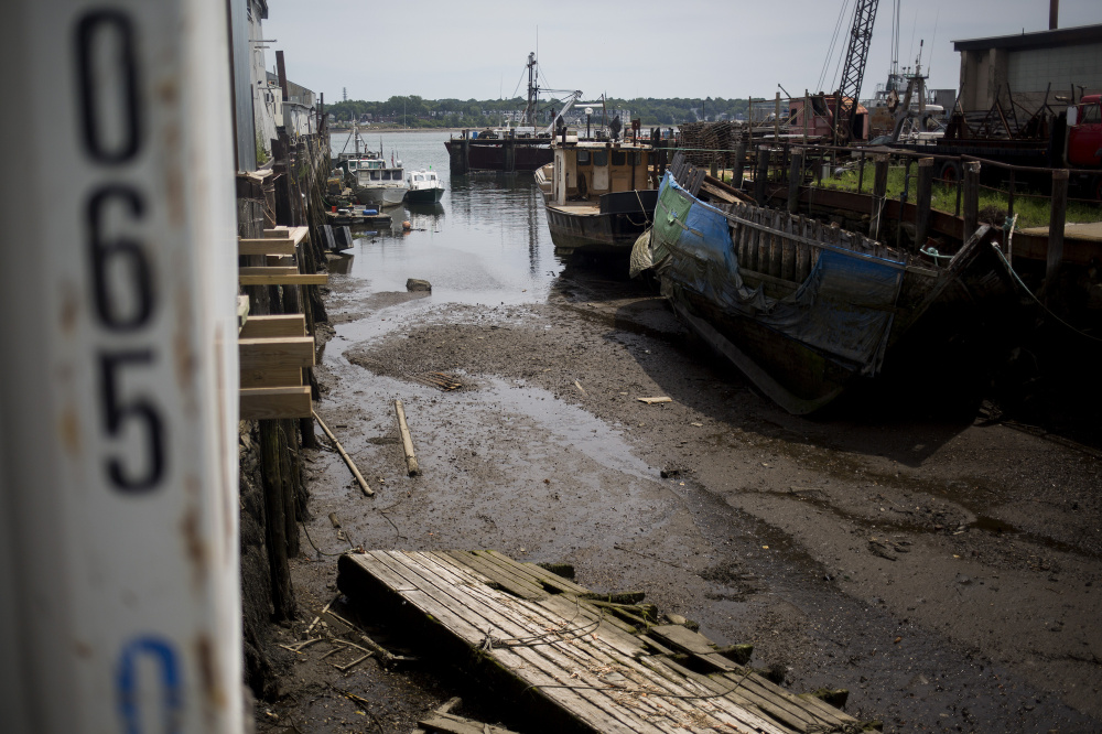 Boats lie in silt during low tide at Sturdivant's Wharf along Portland Harbor. Numerous public and private wharves have lost valuable berthing spaces as silt carried down the Fore River and from occasional sewer and stormwater runoff has built up around them.