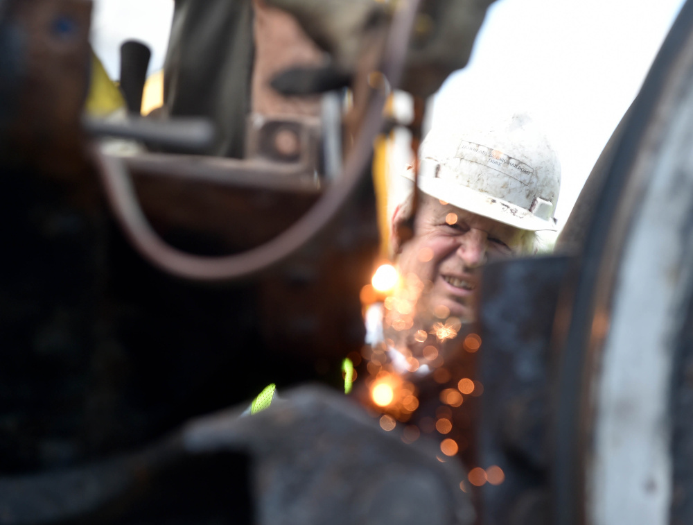 A volunteer from New England Steam Corporation watches as a worker cuts the ash plate from the body of the Old 470 locomotive at the rail yard on College Avenue in Waterville on Monday. The train, which has sat for more than 60 years since its last run, will be shipped to Ellsworth by truck to be restored.