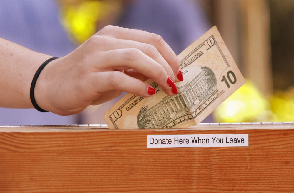A patron deposits money into a donation box at the cafe. Gregory Rec/Staff Photographer