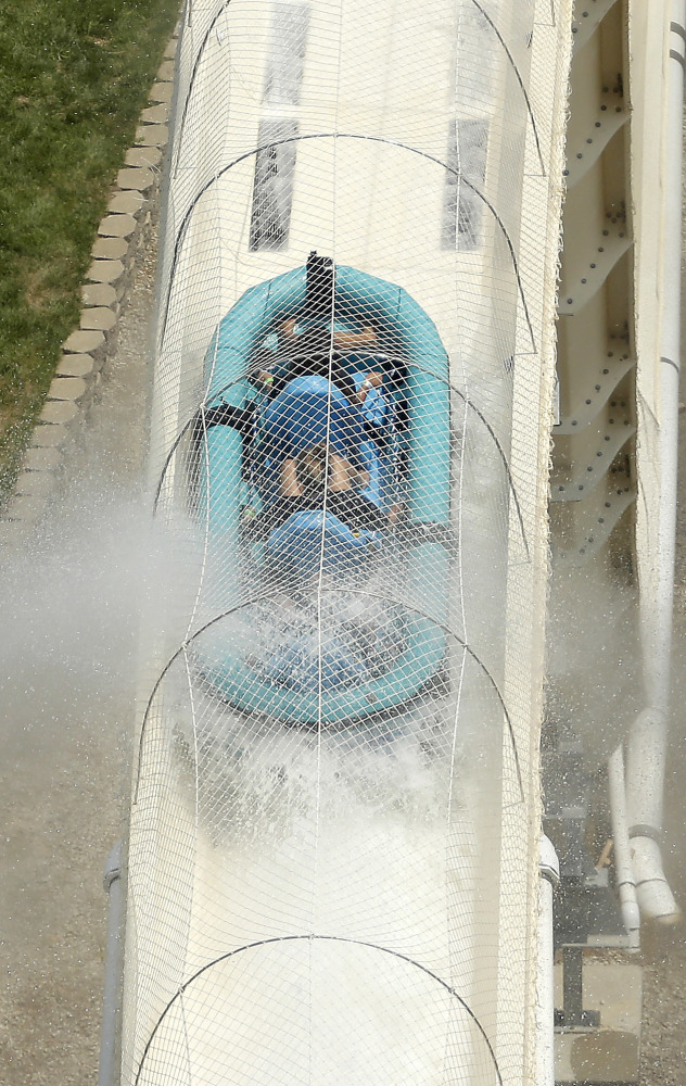 Riders propelled by jets of water go over a hump while riding a raft waterslide called