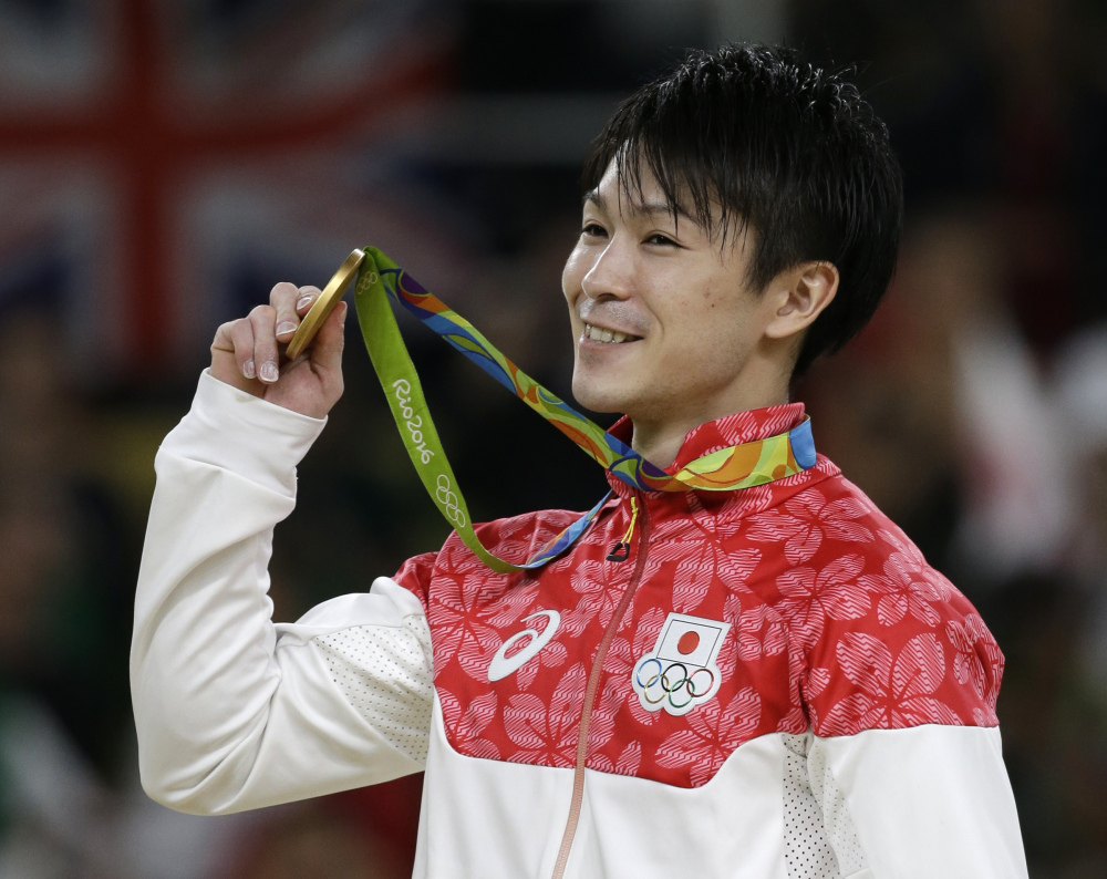 Japan's Kohei Uchimura displays his gold medal Wednesday after winning the artistic gymnastics men's individual all-around final in Rio de Janeiro