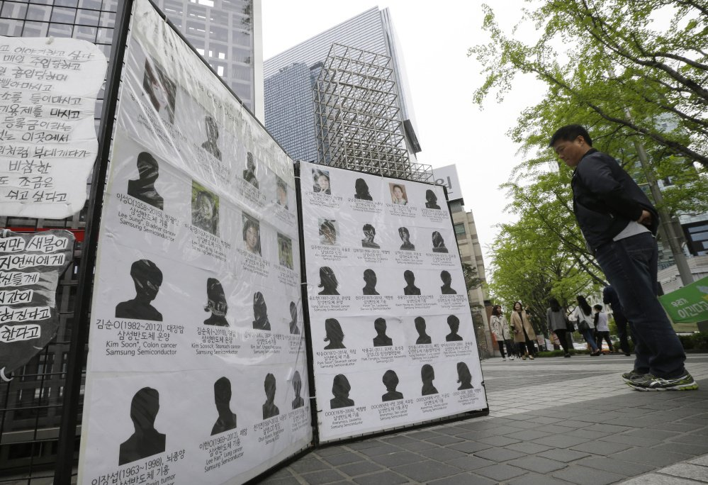 Outside Samsung offices in Seoul, South Korea, a man views victims who were former factory employees of the electronics giant. More than 200 cases of serious illness have been documented and 76 people have died, most in their 20s and 30s.
