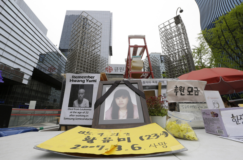 Portraits of former semiconductor factory worker Hwang Yu-mi, who died in 2007, are displayed near Samsung offices in Seoul, South Korea.