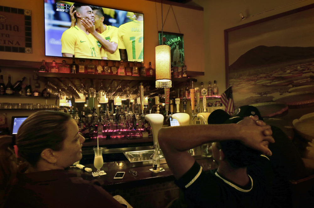 Camila Ornelas, left, and Vander Junior, right, both originally of Brazil, watch a televised soccer match between Brazil and Denmark at the Rio Olympics while sitting at the bar in the Tropical Cafe, in Framingham, Mass. There is pride of the Rio Olympics in this Boston bedroom community, nicknamed