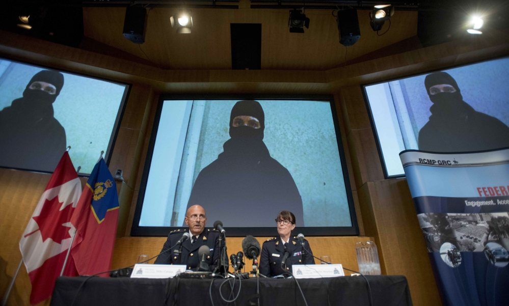 Video footage showing Aaron Driver is seen behind Royal Canadian Mounted Police Deputy Commissioner Mike Cabana, left, and Assistant Commissioner Jennifer Strachan during a news conference in Ottawa for what the RCMP are calling a terrorism incident in Strathroy, Ontario.