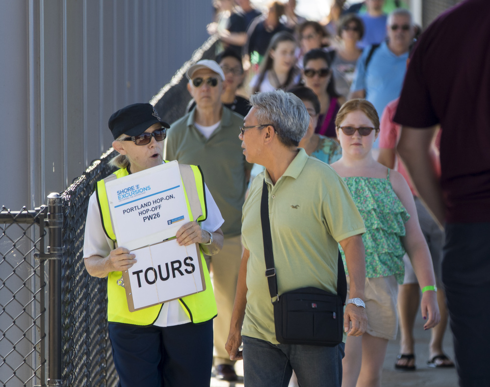 Greeter Julie Amergian offers directions to cruise ship passengers at Ocean Gateway. A cruise industry watchdog says Maine has done well in passing regulations to try to protect its waters from ship pollution.