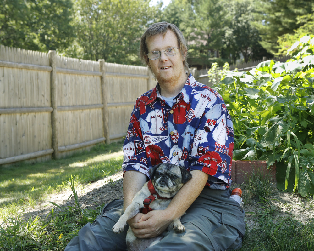 Greg Rogers, 45, poses with his dog Zambi next to his garden at his home in Portland. Rogers grows vegetables for a local food pantry and volunteers with Garbage to Garden. Joel Page/Staff Photographer