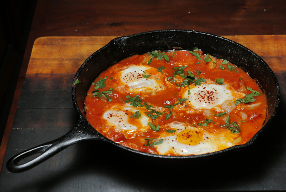 Eggs poached in buttery tomatoes with onion and cumin.