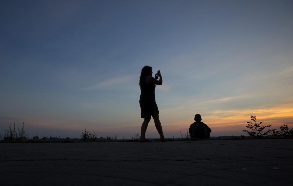 Nicole Cardelfe of Burlington, Vt., takes photos of the sunset Thursday from Fort Sumner Park in Portland. The Munjoy Hill Neighborhood Organization plans to work with the developer in hopes of avoiding a bitter public battle over a proposed condo complex that would obscure the view.