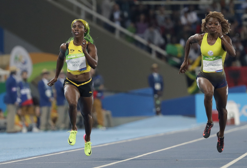 Jamaica's Shelly-Ann Fraser-Pryce, left, and Ecuador's Narcisa Landazuri run in a women's 100-meter heat Friday night. Fraser-Pryce, the only woman to beat 11 seconds, advanced in her bid to become the only woman to win the same individual track event in three straight Olympics.
