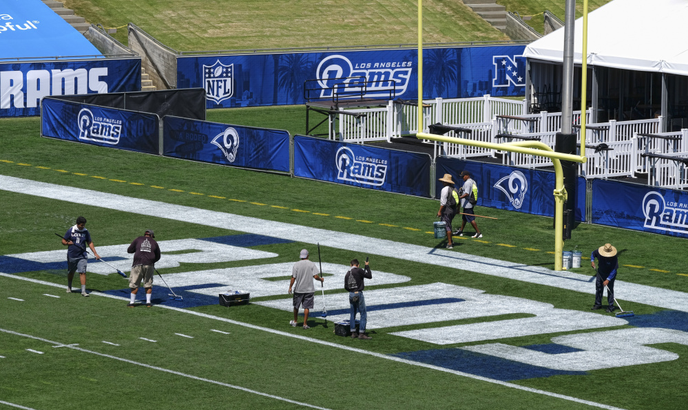 Crew members paint the end zone with the Rams lettering at the Los Angeles Memorial Coliseum – the team's former home – in preparation for a preseason game against the Dallas Cowboys.