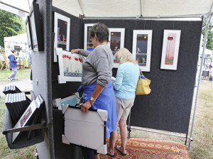 Leslie Sederland of Scarborough and Charleen Kress of Mass. look through works by artist Peyton Higgison of Brunswick at South Portland's Art in the Park at Mill Creek Pond.