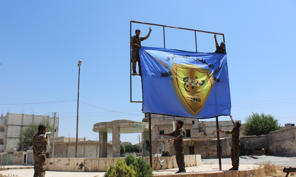 Kurdish-led Syria Democratic Forces raise their flag in the center of the town of Manbij after driving Islamic State militants out of the key Islamic State stronghold in Aleppo province in northern Syria following two months of heavy fighting.